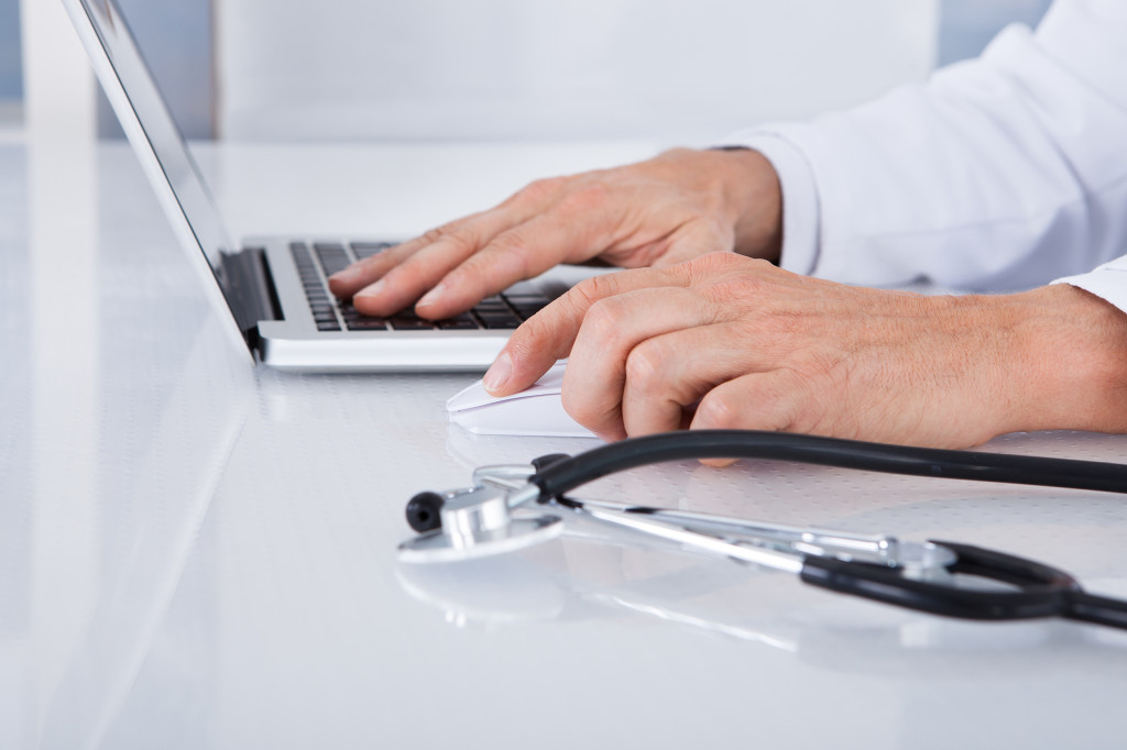 Image of the hands on a keyboard, with a stethescope nearby. A health professional using computer